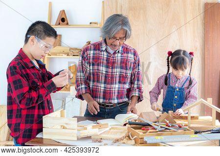 Asian Senior Carpenter Man Teaching Asian Kid Craftswoman Make  Wooden Toys At Carpentry Shop. Famil