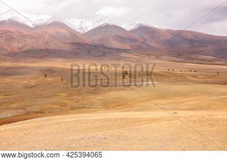A Look At The Deserted Autumn Steppe At The Foot Of The Mountain Range With Snow-capped Peaks.