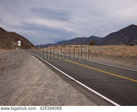 Straight Two-lane Asphalt Road With Signs Going Through The Valley Into The Mountains Above Which A