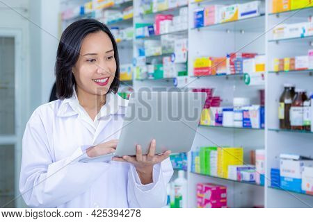 Asian Pharmacists Are Using A Laptop For Work In A Pharmacy. Health Care And Medical Concept.