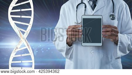 Mid section of male doctor holding a digital tablet against dna structure on purple background. medical research and science technology concept