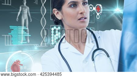 Digital interface with medical data processing against female doctor examining x-ray report. medical research and science technology concept