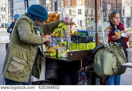 Copenhagen, Denmark - Oct 21, 2018: Street Vendor Manually Squeezing And Selling Fresh Orange Juice
