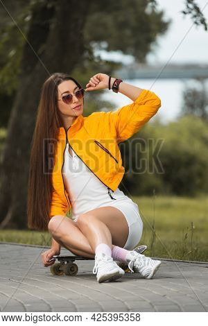 Attractive Woman  In Short Dress And Sunglasses Sitting On The Skateboard And Looking Away Smiling W