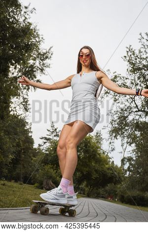 Attractive Woman  In Short Dress And Sunglasses Riding  On The Skateboard And Looking Away Smiling W