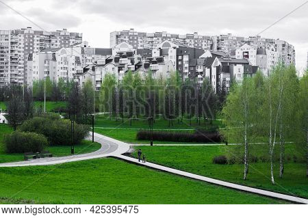 Public Park With Grass, Trees, Walking Path, Footpath, Trail In Front Of A Multi-storey Residential