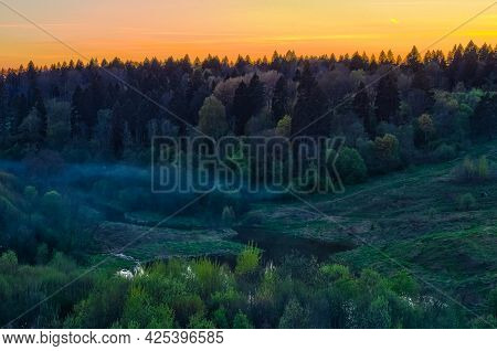 Landscape With Forest Hills In Evening. Fog Over A Small River In The Middle Of The Forest. Sunset S
