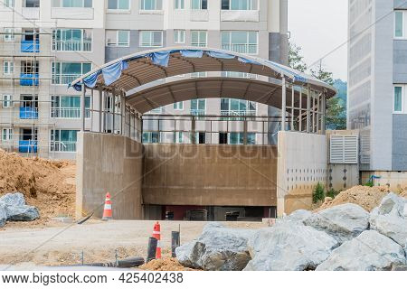 Covered Entrance Ramp To Underground Parking At Construction Site Of Highrise Apartments.