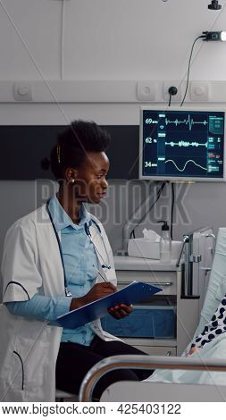 Afro American Doctor Writing Medical Expertise On Clipboard Monitoring Disease Symptom Working In Ho
