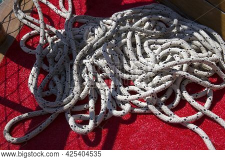 Close-up Of A Nautical Mooring Rope With A Knotted End Tied Around A Cleat On Red Wooden Pier Nautic