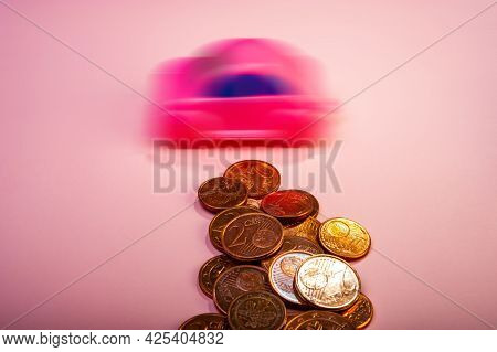 Euro Cent Coins And A Blurred Toy Car Lie On A Pink Background. Business Concept. Background For Des