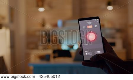 Man Holding Smartphone With Lighting Control Application, Turning On The Lights Sitting In Kitchen H