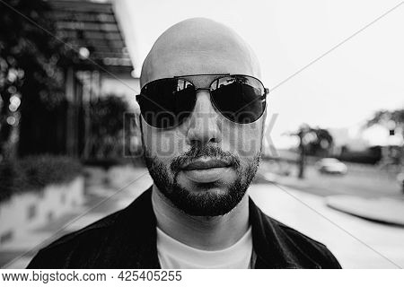 Confident Young Caucasian Man In Sunglasses, Standing In The Street. Handsome Bald Male Model In Sha