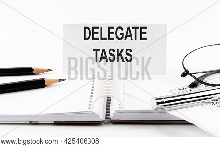 Text Delegate Tasks On Paper Card,pen, Pencils, Glasses,financial Documentation On The Table - Busin
