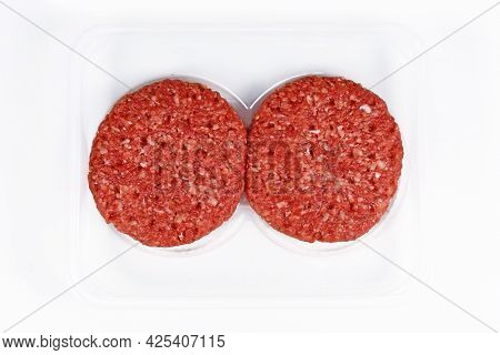 Two Raw Round Burger Patties In Package On White Background