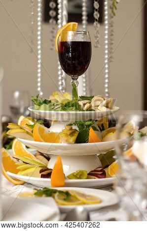 Glass Of Red Wine With A Slice Of Orange On A Plate With Fruit, Bananas, Kiwi, Pear, Apple, Orange,