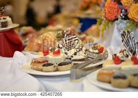 Sweet Snacks Various Small Cakes With Butter Cream And Chocolate On A Plate On A Banquet Table In A