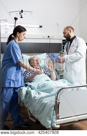 Medical Team Helping Senior Woman Patient Laying In Hospital Bed, To Breath With Espiratory Mask Wit