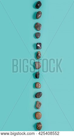 Small Stones Similar To Pebbles Lying On A Turquoise Background Vertically. Vertical Picture With St