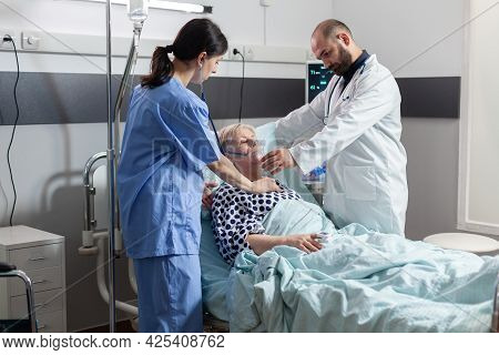Unconscious Senior Woman Patient Laying In Hospital Bed And Medical Staff Is Helping Her Breath Usin
