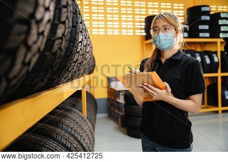 Asian Female Worker Wear A Mask To Prevent The Spread Of Corona Virus Or Covid-19 Is Checking The St