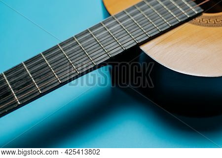Close-up Of Acoustic Guitar Neck On Blue Background
