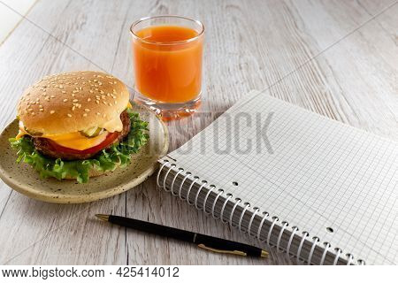 A Quick Snack For Businessmen, Schoolchildren, Students. Notebook, Delicious And Healthy Burger And