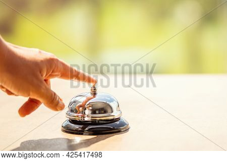 Woman Ringing Hotel Bell Of Summer Beach Hotel Front Desk. Coastline Sea And Palm Tree View. Travel