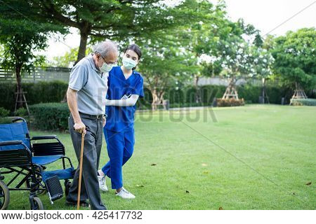 Asian Young Woman Nurse Taking Care And Support Disabled Senior Elderly Man On Wheelchair At Backyar