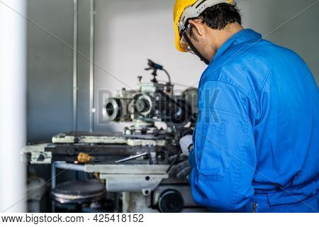 Asian Mechanical Worker Male Working On Milling Machine In Factory. Technicians Wear Protective Glas