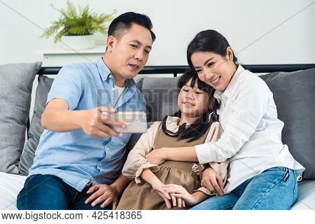 Asian Parents And Little Kid Use Telephone Video Call Online To Family. Loving Father Mother And You