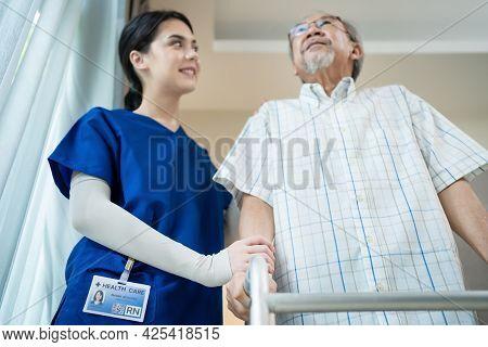 Asian Nurse Support Elder Disable Man Walk With Walker At Nursing Home. Caregiver Therapist Doctor H