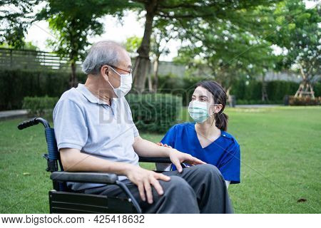 Asian Caregiver Wear Mask, Take Care Senior Disabled Man On Wheelchair. Young Beautiful Woman Carer