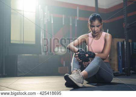 Asian Active Fitness Sportswoman Trainer Sit On Floor Of Dark Stadium. Bodybuilder Athlete Sport Gir
