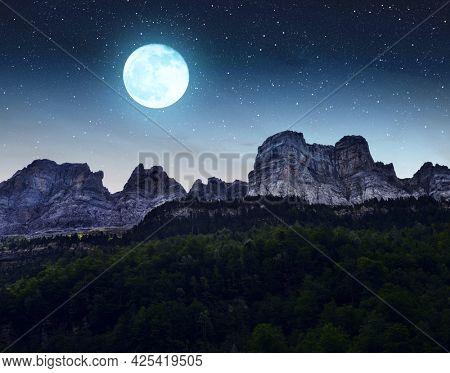 Mountain landscape in the night sky with moon. Ordesa y Monte Perdido National park, Huesca, Aragon, Spain.