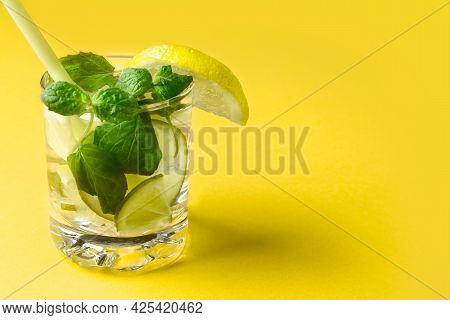 Citrus Water With Lemon, Lime And Mint. A Glass Of Lemonade On A Yellow Background. Vitamin Drink. H