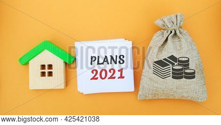 A Note With The Words Plans 2021, A House And A Money Bag. Real Estate Concept. Family Budget Planni