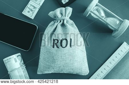 Money Bag With The Word Roi. Return On Investment Concept. Profitability And Loss-making Of Investme