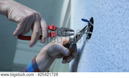 A Man In A Plaid Shirt Works With Electrical Wires Using Tools, Fixing A Wall Switch Or Socket At Ho