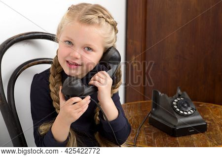 Blonde Girl Talking By Old Black Phone. Lovely Girl With Braids Sitting On Chair In Vintage Room Int
