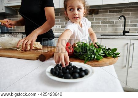 Little Girl Eating Olives? Pizza Ingredient, While Mom Prepares Pizza Dough
