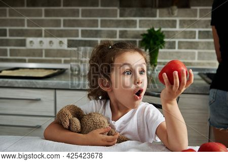 Cute Baby Girl Hugging Her Soft Plush Toy And Looking At Ripe Red Tomato In Her Hand Sitting At A Ki