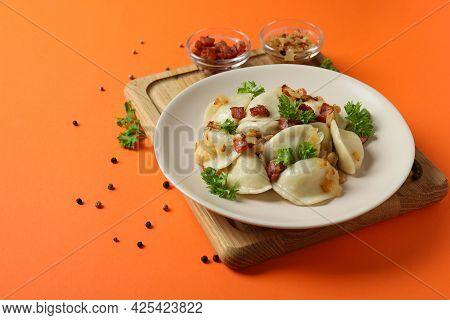 Concept Of Tasty Food With Vareniki Or Pierogi On Orange Background