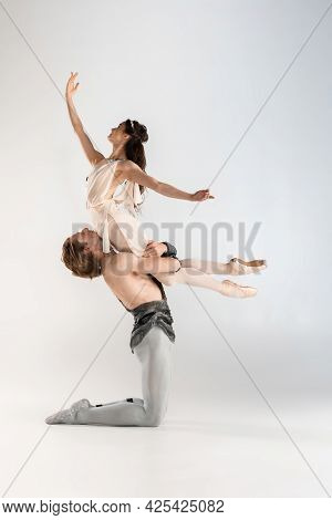 Young Couple Of Ballet Dancers In Ancient Rome Costumes Dancing On White Studio Full Of Light. Histo
