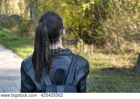 Girl With Ponytail Is Walking In The Park. Young Girl Student Stands In The Park. Back View