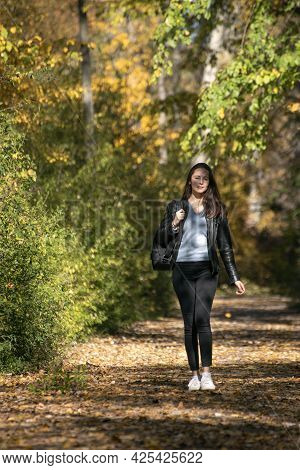 Beautiful Young Woman With Dark Hair Walks Along The Alley Of An Autumn Park And Enjoys A Warm Day.