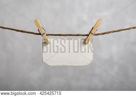 Small Nameplate Hanging With Clothespins On Rope. Blank White Sign, Plate For An Inscription. Copy S