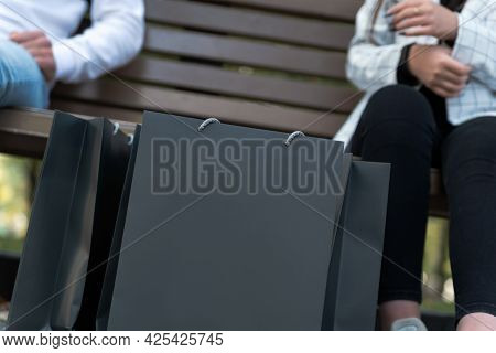 Black Paper Shopping Bags On The Background Of People. Young Man And Woman After Shopping. Mock Up.