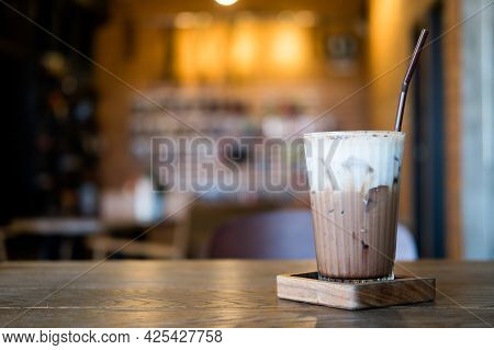 Iced Mocha With Milk Foam On Top And Blur Lighting Cafe