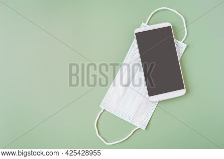 White Smart Phone With Clipping Path On Touchscreen On Face Mask On Green Background For New Normal